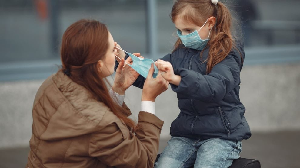 Child putting face mask on adult