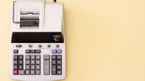 Calculator working out tax on yellow background